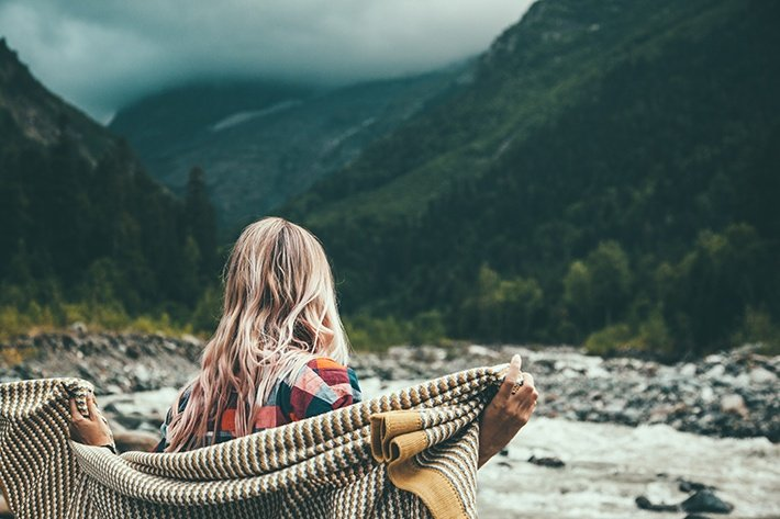 Girl wrapping in warm blanket outdoor, hiking in mountains, bad