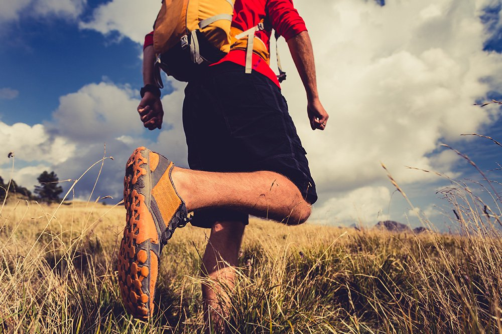 Hiking man or trail runner walking in mountain inspirational landscape. Fitness and healthy lifestyle hiker or trekker walk on dry grass fall autumn nature.