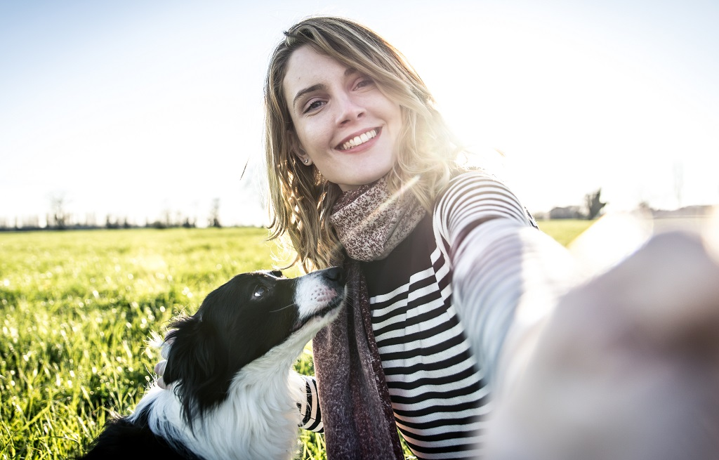 Woman playing with her border collie and taking selfies