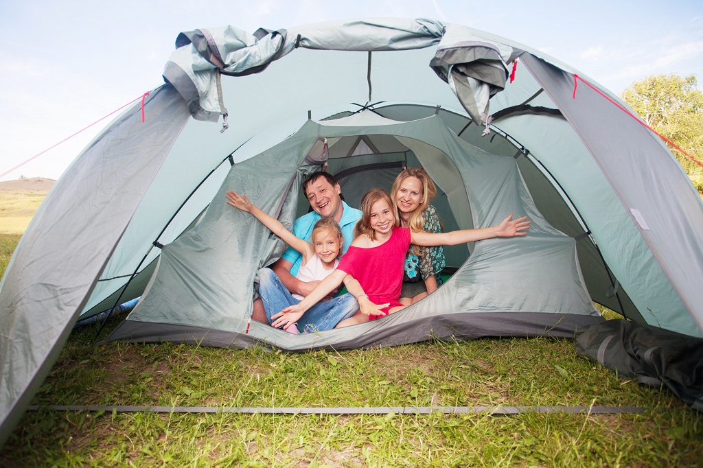 Family with children in a tent. Camping. Happy parents with kids