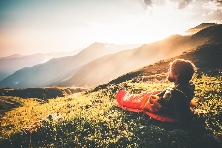 Man-relaxing-in-sleeping-bag-enjoying-sunset-mountains-landscape