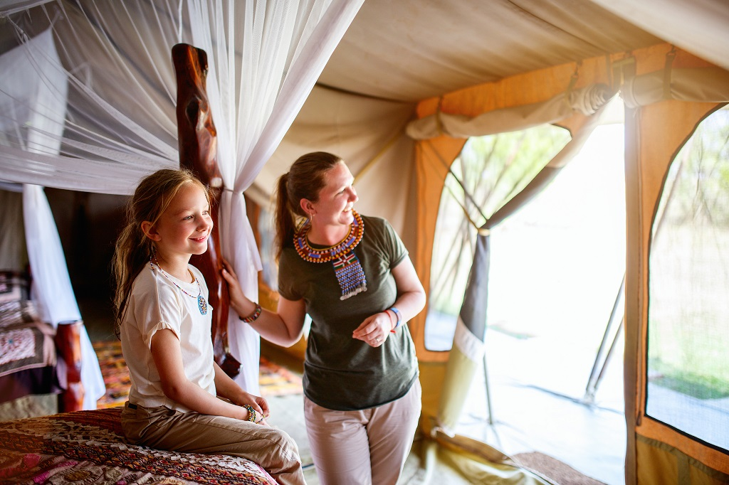 Family mother and her child in safari tent enjoying vacation in
