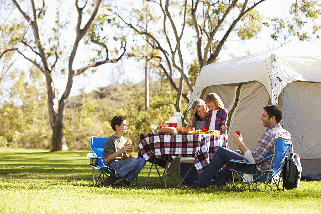 Family Enjoying Camping Holiday In Countryside