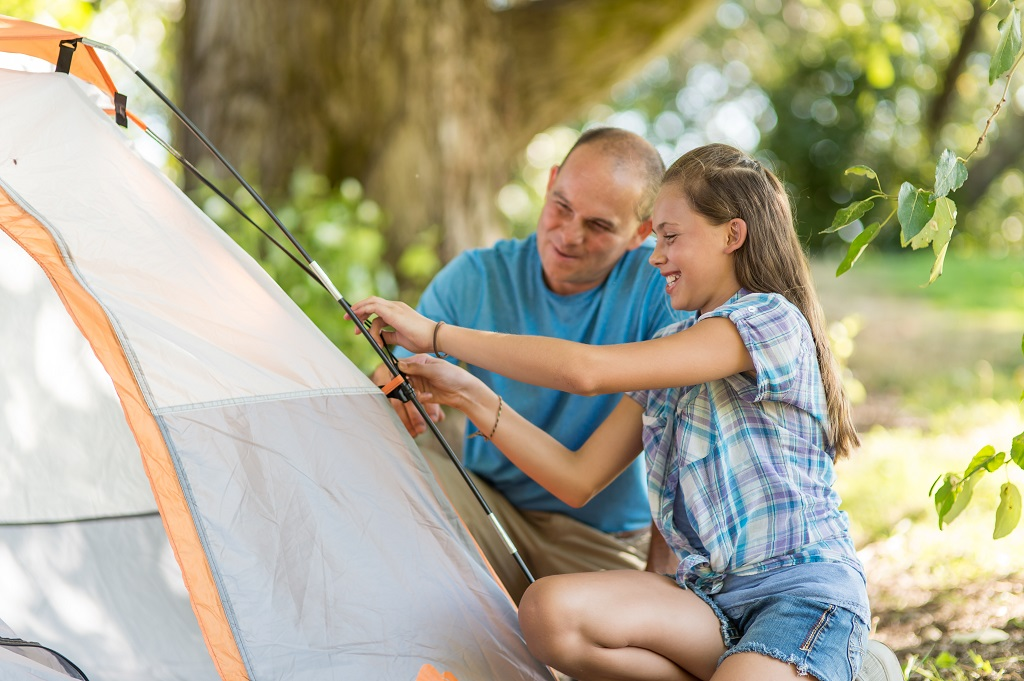 Father and daughter setting up tent together